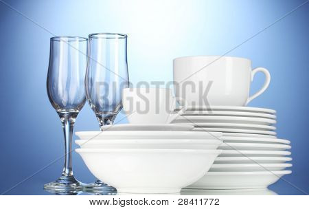 empty bowls, plates, cups and glasses on blue background
