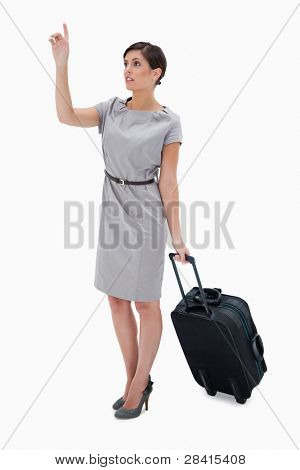 Woman with wheely bag calling a taxi against a white background