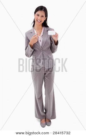 Smiling businesswoman pointing at blank name badge against a white background