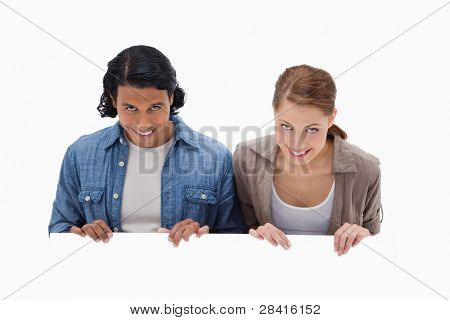 Smiling couple looking over blank wall against a white background