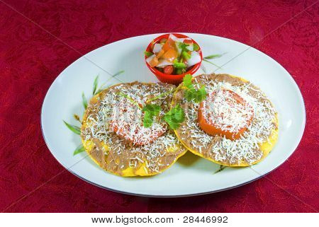 Traditional Honduran food, Catrachitas, on plate with rich red background.