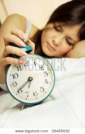 young woman switches off the alarm clock in the morning and keeps sleeping