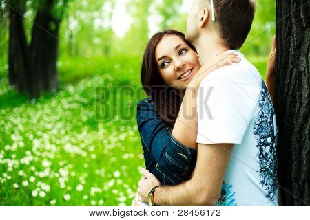 beautiful young romantic couple having a walk in summer park