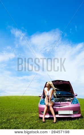 beautiful young woman repairing her car outdoor on a summer day