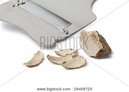 Truffle and slicer on white background
