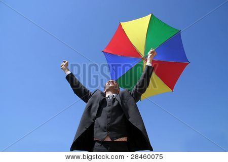 Sucess business man with coloured umbrella and arms wide open