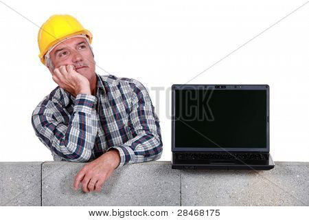 Builder with a laptop showing a blank screen