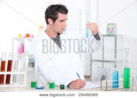 Young man studying the contents of a test tube and making notes accordingly