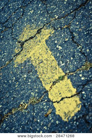 Yellow Painted Arrow On Cracked Pavement