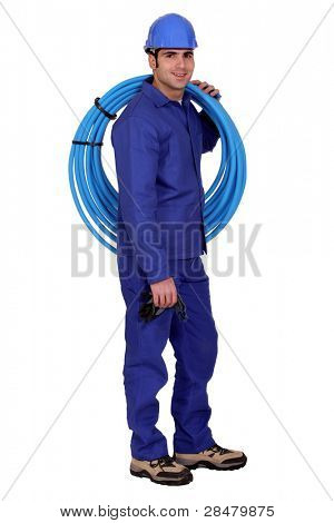 Plumber with a reel of blue pipe