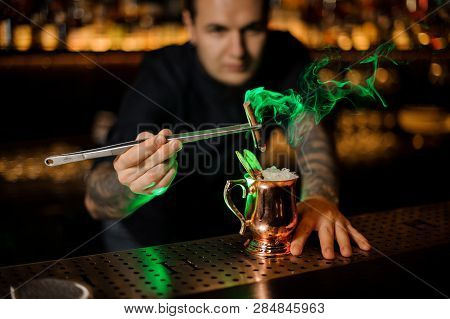 Bartender Adding To The Cocktail