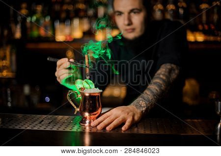 Barman Adding To A Cocktail
