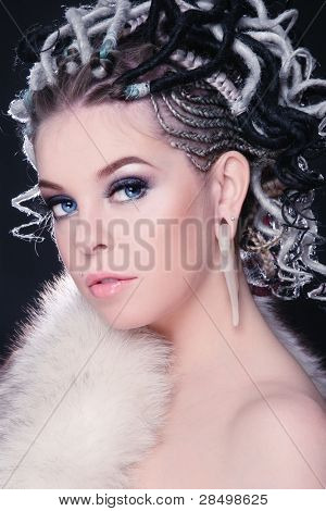 Beautiful young sexy girl with fancy hairstyle of dreads and white fur on her body