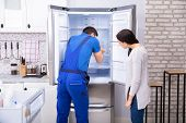 Woman Looking At Male Repairman Fixing Refrigerator With Screwdriver poster