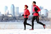 Runners running in winter snow with city skyline background. Healthy multiracial young couple. Asian