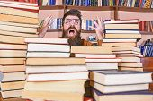 Man On Shocked Face Between Piles Of Books In Library, Bookshelves On Background. Teacher Or Student poster