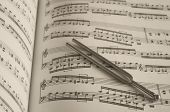 pic of tuning fork  - Tuning fork on classic sheet music background - JPG
