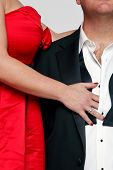 Photo of a woman in a red dress with red fingernails unbuttoning the shirt of a man wearing a tuxedo