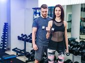 A Sport Man And Girl Fitness Training In Gym With Together Trainer And Using Dumbbell And Weightlift poster
