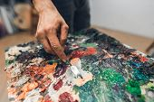 Background. The Hand Of The Artists Man From The Palette Knife Mixes The Paint On The Palette Close poster