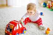 Adorable Cute Beautiful Little Baby Girl Playing With Educational Wooden Toys At Home Or Nursery. He poster