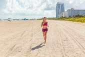Fit woman training outdoors running barefoot on Miami south beach run jogging workout female Asian a poster