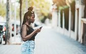 A Cute Young Black Girl With Braided Hair Is Standing On A Bright City Street Is Checking Her Route  poster