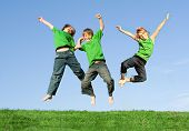 image of triplets  - happy smiling group of children or kids jumping outdoors