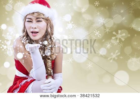 Sexy Santa Blowing Snow In Golden Lights Background
