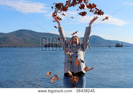 Young woman throwing leaves into the crisp fall air