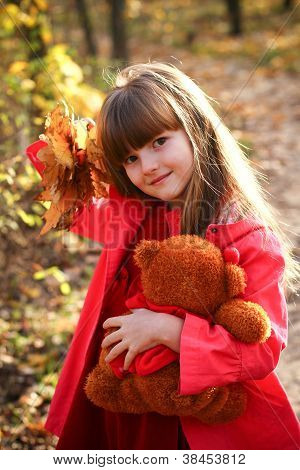 The Little Girl In The Autumn Forest With Maple Leaves And Teddy Bear