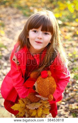 Surprised Little Girl With Maple Leaves And Teddy Bear In The Autumn Forest