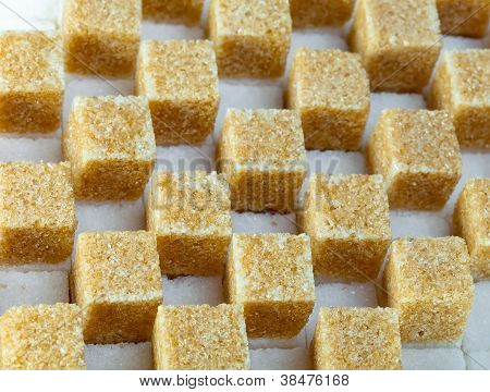 Cubes of not refined reed sugar lie on pieces of white sugar