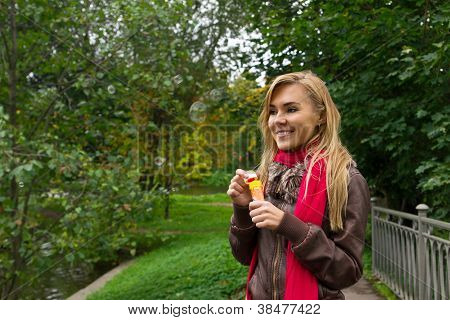 Young Pretty Blond Woman Blowing Soap Bubbles in park