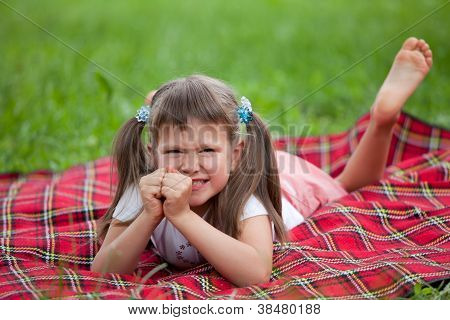 Little Irritated Girl Preschooler Lying On Plaid And Grass
