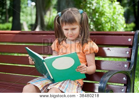 Little Cute Girl Preschooler With Book On Bench In Park