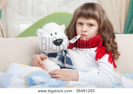 Little Sick Girl With Thermometer Embraces Toy Bear In Bed