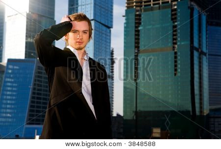 Portrait Of Young Quiet Businessman By Skyscraper In City