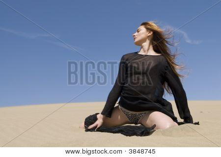 Beautiful Woman In Black In The Desert Dunes