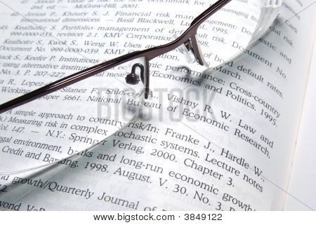 Glasses Laying On Financial Book.