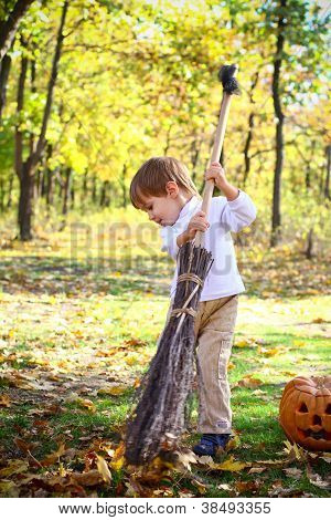 Little Boy With Haloween Pumpkin And A Broom In The Forest
