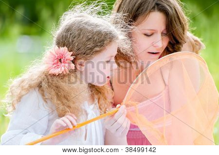 Little Girl And Her Mother With Butterfly Net