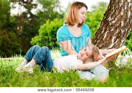 Mother Reading Book To Her Daughter