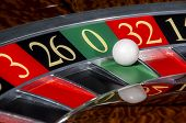 image of roulette table  - Classic casino roulette wheel with sector zero and white ball - JPG