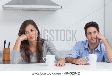 Tired couple sitting at the table with a cup of coffee in the kitchen