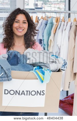 Woman volunteer smiling and holding donation box