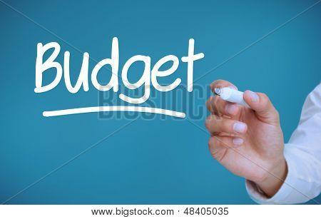 Mão escrevendo orçamento sobre fundo azul