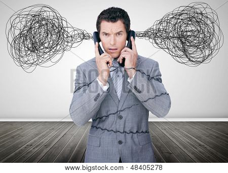 Overworked businessman holding two telephones and looking at camera