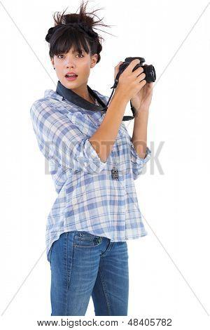 Erstaunt junge Frau, die Aufnahme mit ihrer Kamera auf weißem Hintergrund