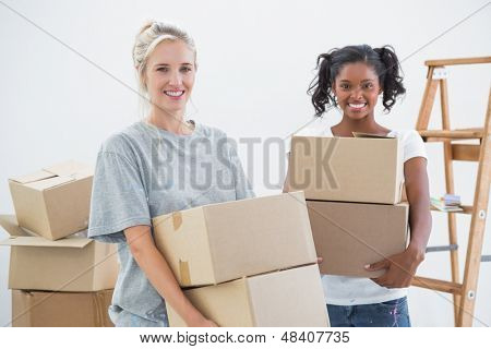 Cheerful housemates carrying moving boxes and smiling at camera in new home